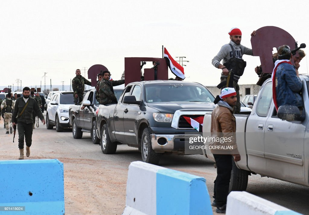 A picture taken on February 20, 2018 shows a convoy of pro-Syrian government fighters arriving in Syria's northern region of Afrin. Kurdish forces said in a statement on February 20 that pro-regime fighters deployed to Syria's Afrin region will take up positions and 'participate in defending the territorial unity of Syria and its borders', countering Turkey's offensive on the area. / AFP PHOTO / George OURFALIAN / The erroneous mention[s] appearing in the metadata of this photo by George OURFALIAN has been modified in AFP systems in the following manner: [region of Afrin] instead of [city of Afrin]. Please immediately remove the erroneous mention[s] from all your online services and delete it (them) from your servers. If you have been authorized by AFP to distribute it (them) to third parties, please ensure that the same actions are carried out by them. Failure to promptly comply with these instructions will entail liability on your part for any continued or post notification usage. Therefore we thank you very much for all your attention and prompt action. We are sorry for the inconvenience this notification may cause and remain at your disposal for any further information you may require.