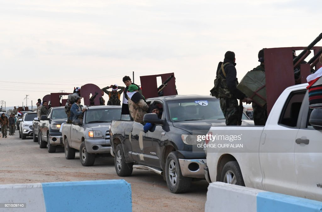 A picture taken on February 20, 2018 shows a convoy of pro-Syrian government fighters arriving in Syria's northern region of Afrin. Kurdish forces said in a statement on February 20 that pro-regime fighters deployed to Syria's Afrin region will take up positions and 'participate in defending the territorial unity of Syria and its borders', countering Turkey's offensive on the area. / AFP PHOTO / George OURFALIAN