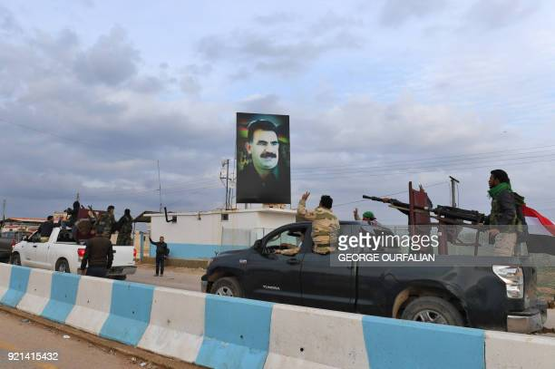 TOPSHOT A picture taken on February 20 2018 shows a convoy of proSyrian government fighters flashing the victory gesture as they ride through the...