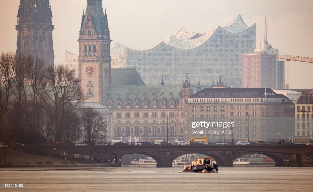 A picture taken on February 20, 2018 shows a view of the city of Hamburg, northern Germany, with St. Nikolai memorial (L), the Kennedy bridge (front) and the Elbphilharmonie concert hall in the background. / AFP PHOTO / dpa / Daniel Reinhardt / Germany OUT