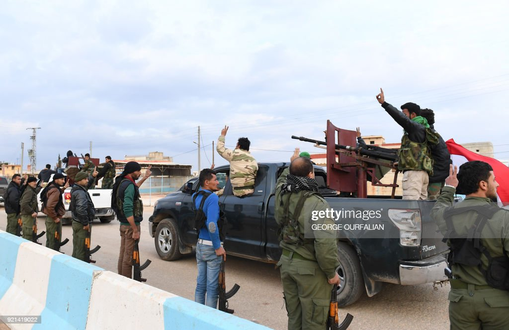 A picture taken on February 20, 2018 shows Kurdish fighters flashing the victory gesture as they welcome a convoy of pro-Syrian government fighters arriving in Syria's northern region of Afrin. Kurdish forces said in a statement on February 20 that pro-regime fighters deployed to Syria's Afrin region will take up positions and 'participate in defending the territorial unity of Syria and its borders', countering Turkey's offensive on the area. / AFP PHOTO / George OURFALIAN