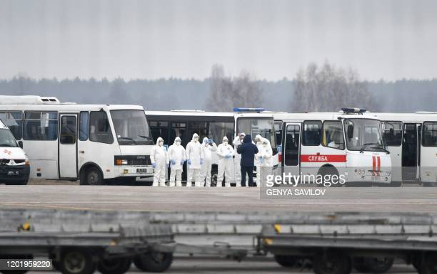 A picture taken on February 20 2020 through a fence at the Kiev international airport Boryspil shows airport crew members and emergency services in...