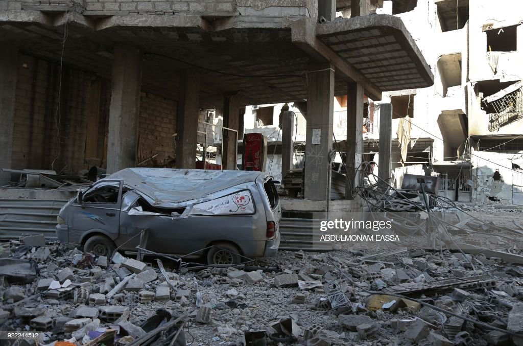 A picture taken on February 21, 2018 shows a damaged make-shift ambulance vehicle amongst rubble of a destroyed hospital in the rebel-held enclave of Hamouria in the Eastern Ghouta near Damascus, following a reported regime air strike. /