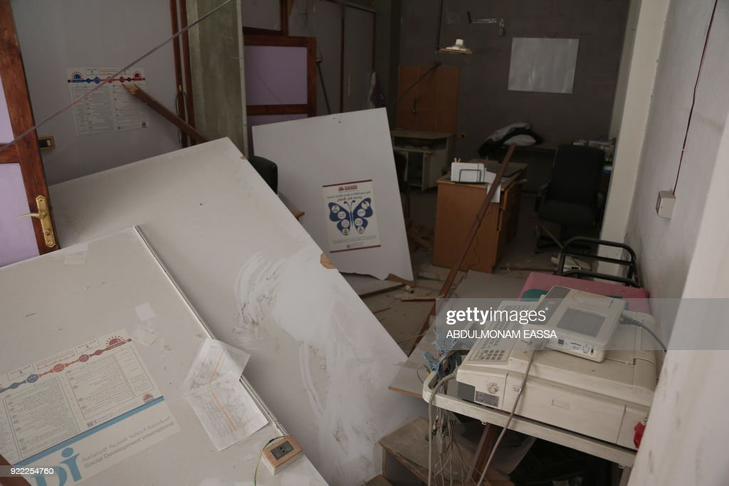 A picture taken on February 21, 2018 shows a view through a heavily damaged room in a pediatric care department in a hospital that was hit by a reported regime air strike in the rebel-held enclave of Hamouria in the Eastern Ghouta near Damascus. /