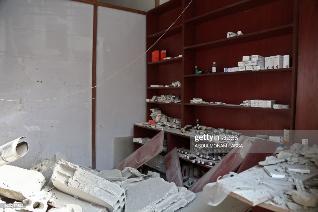 A picture taken on February 21, 2018 shows a view through the wall of a destroyed hospital's pharmacy after it was hit in a reported regime air strike in the rebel-held enclave of Hamouria in the Eastern Ghouta near Damascus. /
