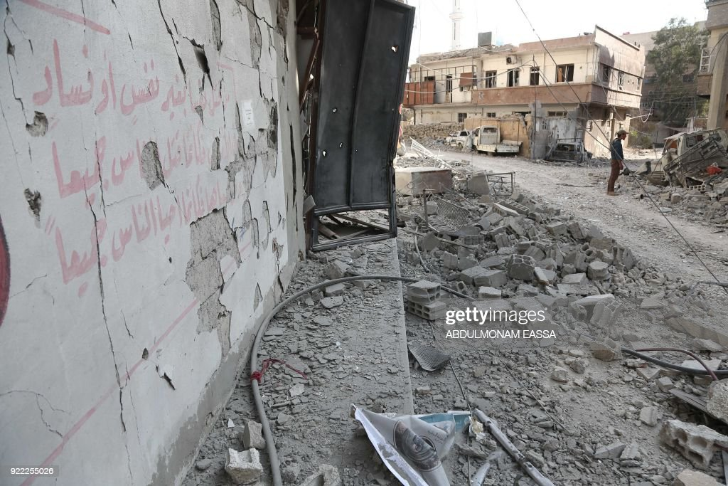 A picture taken on February 21, 2018 shows the damaged wall of a destroyed hospital that was hit by a reported regime air strike in the rebel-held enclave of Hamouria in the Eastern Ghouta near Damascus, with a mural written in Arabic of a Quran verse reading: 'Whoever kills a person [unjustly] is as though he has killed all mankind. And whoever saves a life, it is as though he had saved all mankind.' /