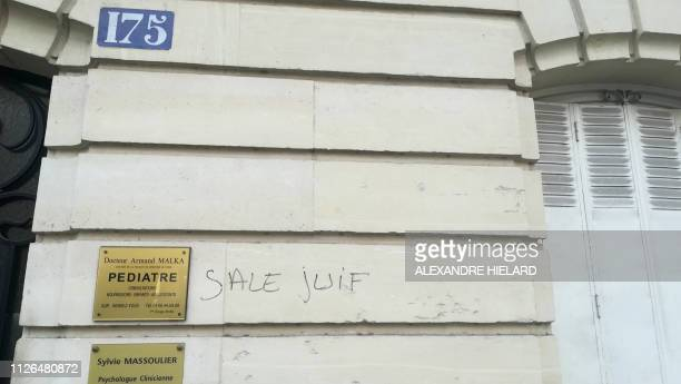 A picture taken on February 21 2019 in the rue d'Alesia in the 14th arrondissement of Paris shows an antiSemitic tag reading dirty Jew on a building...