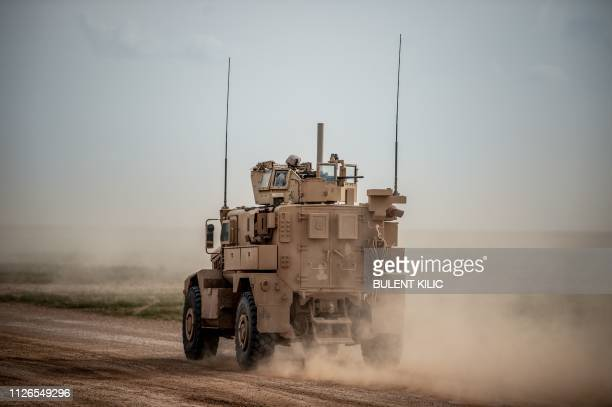 A picture taken on February 21 2019 shows a US soldier atop an armoured vehicle as it drives on a road in Syria's northern Deir Ezzor province...