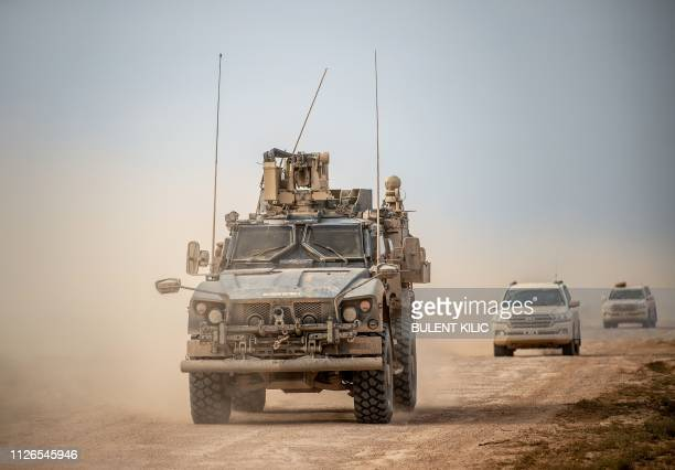 A picture taken on February 21 2019 shows vehicles belonging to the USbacked coalition as they drive down a road in Syria's northern Deir Ezzor...