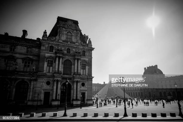 A picture taken on February 22 2018 from a doubledeck tourist bus shows the Louvre museum palace the Louvre Pyramid and the Cour Napoleon in Paris...