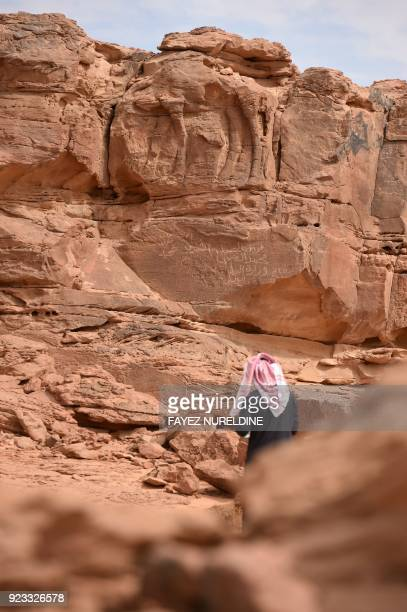 A picture taken on February 22 2018 shows a Saudi man walking at the site of an archaeological discovery about eight kilomtres north of the city of...
