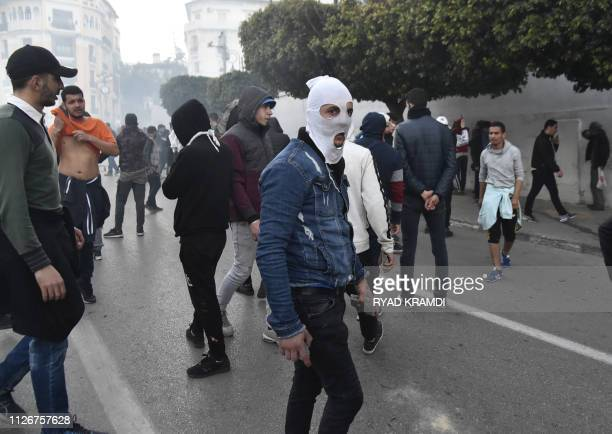 TOPSHOT A picture taken on February 22 2019 shows Algerian protesters as police in riot gear fired tear gas and set up a security cordon to block...