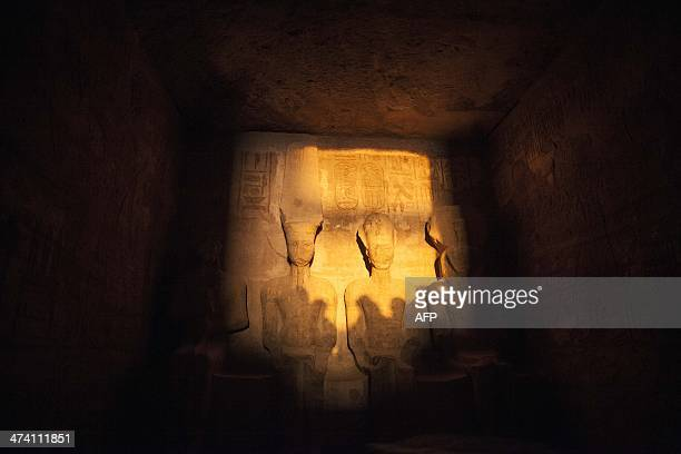 A picture taken on February 22 shows tourists casting their shadows as a ray of light illuminates the statue of Ramses II inside the temple of Abu...