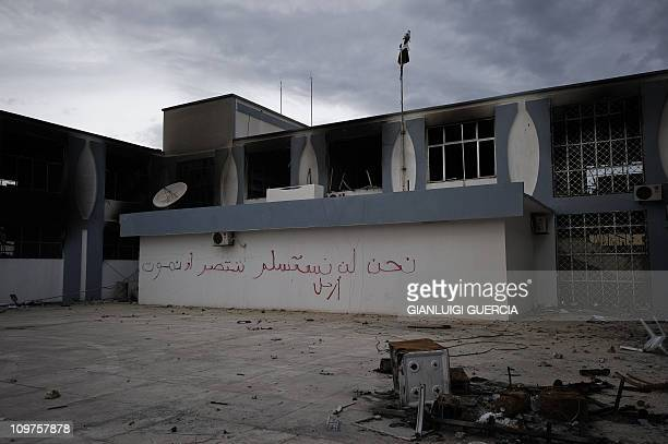 A picture taken on February 23 2011 in the eastern Libyan town of Derna between Tobruk and Benghazi shows a torched government building with Arabic...