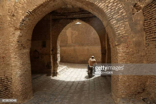 A picture taken on February 24 2018 shows a Yemeni driving a motorcycle in the ancient city of Zabid a UNESCO World Heritage Site currently on the...