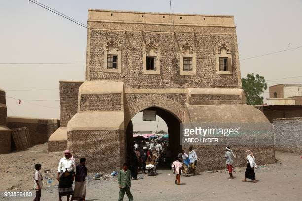 A picture taken on February 24 2018 shows Yemenis walking through a gateway into a market in the ancient city of Zabid a UNESCO World Heritage Site...