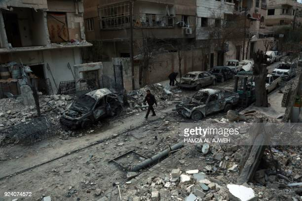 Picture taken on February 25 shows a Syrian man walking next to damaged buildings following regime air strikes in the Syrian rebel-held town of...