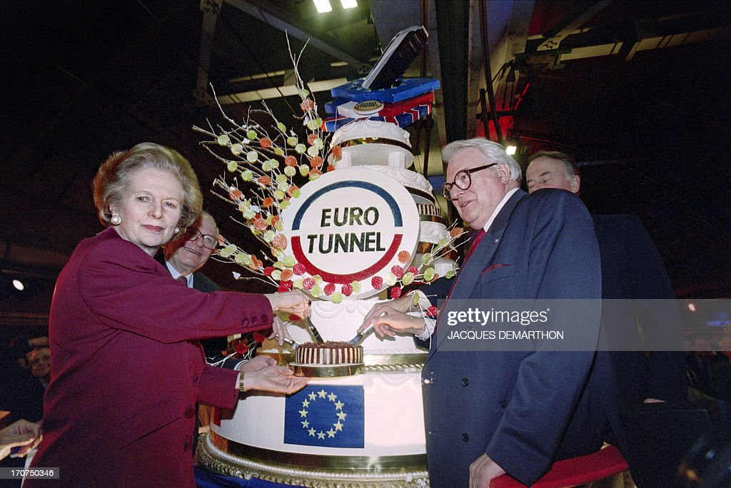 A picture taken on February 26, 1994 shows former British and French Prime Ministers Margaret Thatcher (L) and Pierre Mauroy cutting a cake during the historical lunch offered in Thatcher's honour with 800 prominent guests under the Channel Tunnel, in the British territorial waters, a few weeks before the inauguration. They both had initiated the idea of the Eurotunnel in 1984 during a 'memorable evening in Edimburg'.