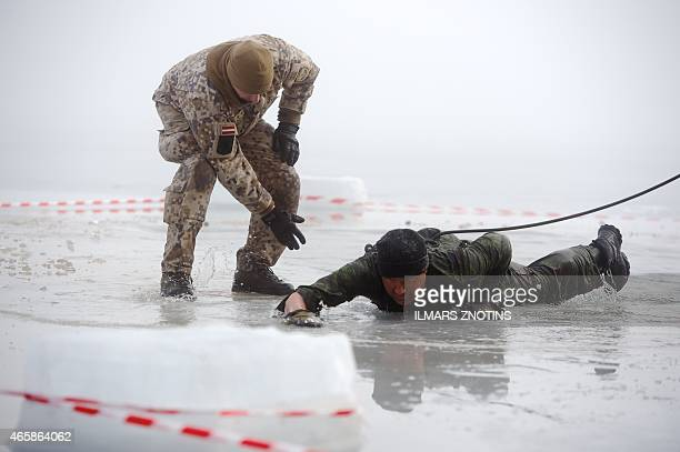 COLLIER Picture taken on February 26 2015 shows soldiers practicing an ice plunge exercise during a training with Latvian US and Canadian soldiers at...