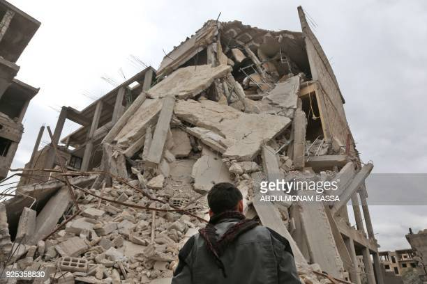 A picture taken on February 26 2018 shows a Syrian youth standing next to the rubble of a destroyed building in Haza in the besieged Eastern Ghouta...