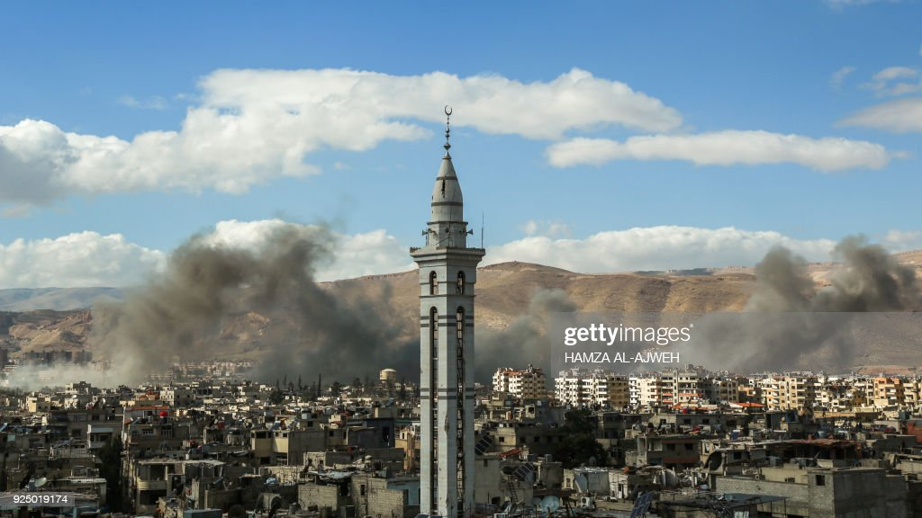 A picture taken on February 27, 2018, shows smoke plumes rising during reported regime bombardment Syrian rebel-held town of Douma, in the besieged Eastern Ghouta region on the outskirts of the capital Damascus. /