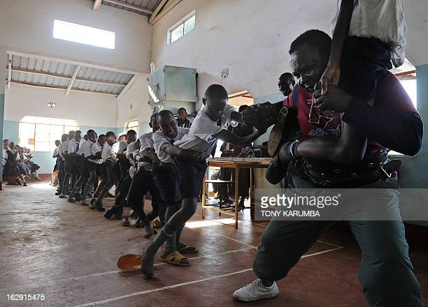 A picture taken on February 28 2013 shows Conrad Njeru Karukenya aka 'Tigerpower' engaging students in a onemantagofwar during a presentation to...