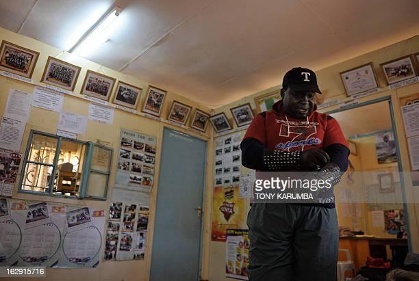 A picture taken on February 28 2013 shows Conrad Njeru Karukenya aka 'Tigerpower' preparing for a presentation to pupils of the Tenri primary school...