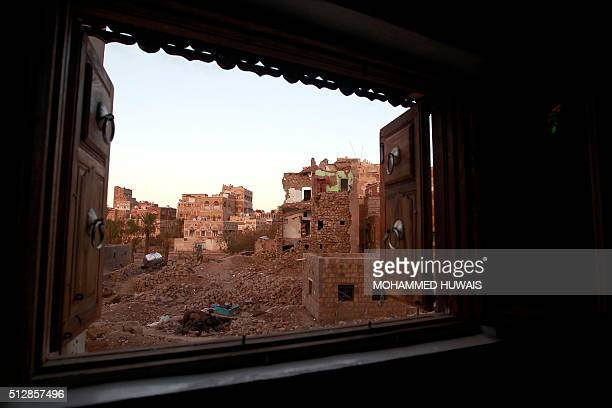 TOPSHOT A picture taken on February 28 2016 shows a window view of damaged houses following air strikes carried out by the Saudiled coalition in the...