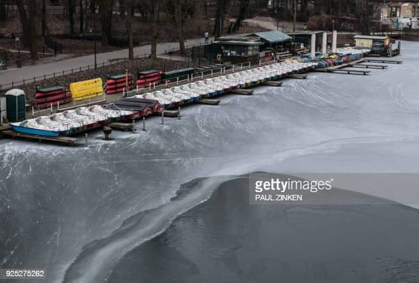 A picture taken on February 28 2018 at Treptower Park in Berlin shows paddle boats on the banks of the Spree river which is partially frozen as...