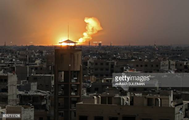 A picture taken on February 28 2018 shows flames erupting in the horizon following a reported rocket attack in alShaffuniyah in the Syrian rebel...
