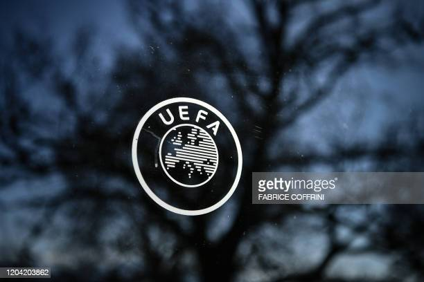 A picture taken on February 28 2020 shows a UEFA sign through a window at the headquarters of the European football's governing body in Nyon