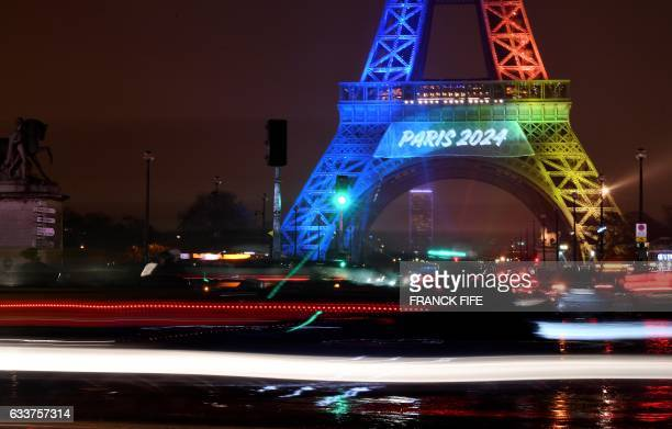 TOPSHOT A picture taken on February 3 2017 shows the Eiffel Tower in Paris lit in the colours of the Olympic flag during the launch of the...