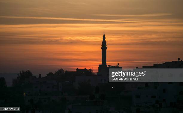 A picture taken on February 3 2018 shows a silhouette view of the village of Burqin in the occupied West Bank about 18 kilometres northwest of Nablus...