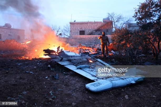 TOPSHOT A picture taken on February 3 shows a Rebel fighter taking a picture of a downed Sukhoi25 fighter jet in Syria's northwest province of Idlib...
