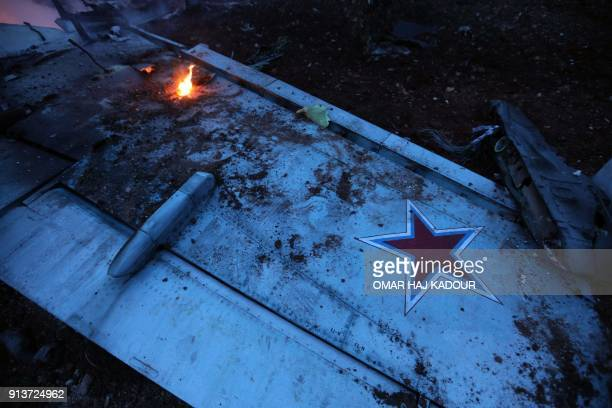 TOPSHOT A picture taken on February 3 shows the wing of a downed Sukhoi25 fighter jet in Syria's northwest province of Idlib Rebel fighters shot down...