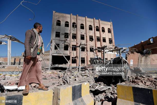 A picture taken on February 5 shows a man standing next to the Yemeni criminal investigations unit in the capital Sanaa a day after it was hit in an...