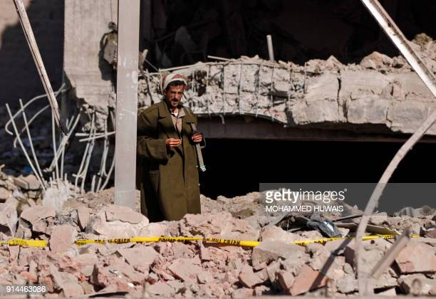 A picture taken on February 5 shows an armed man standing in the rubble of the Yemeni criminal investigations unit in the capital Sanaa a day after...