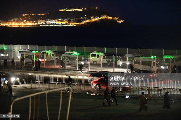 A picture taken on February 6 2014 shows police cars queuing in the border area where eight migrants drowned while trying to swim to the Spanish...