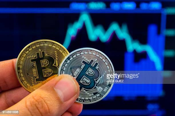 A picture taken on February 6 2018 shows a person holding a visual representation of the digital cryptocurrency Bitcoin at the 'Bitcoin Change' shop...