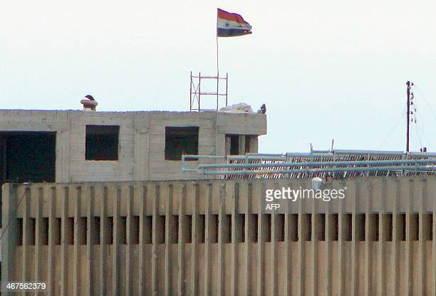 A picture taken on February 6 shows the Syrian national flag waving in the wind over the Aleppo central prison during clashes between proregime...