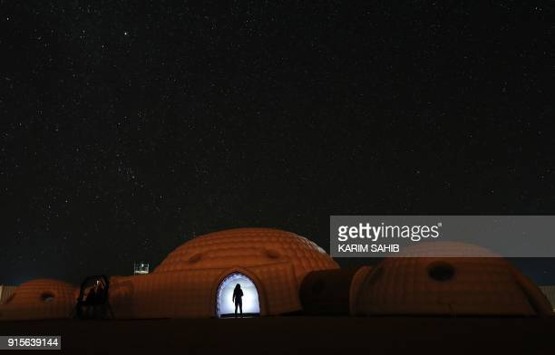 TOPSHOT A picture taken on February 7 2018 shows a member of the AMADEE18 Mars simulation mission wearing a spacesuit standing in the doorway of a...