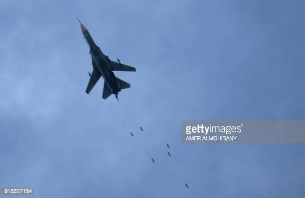 TOPSHOT A picture taken on February 7 2018 shows a Syrian air force MiG23 jet dropping a payload during a reported regime air strike in the rebelheld...