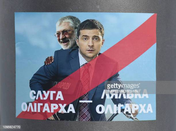 A picture taken on February 8 2019 shows a placard depicting Ukrainian entertainer and presidential candidate Volodymyr Zelensky and oligarch Ihor...
