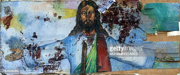 A picture taken on January 1 2011 shows a bloodstained image of Jesus Christ outside the AlQiddissine church which had been the target of an...
