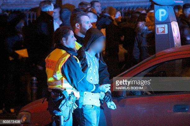 Picture taken on January 1 2016 shows police arresting a man as people gather in front of the main railway station in Cologne western Germany Police...