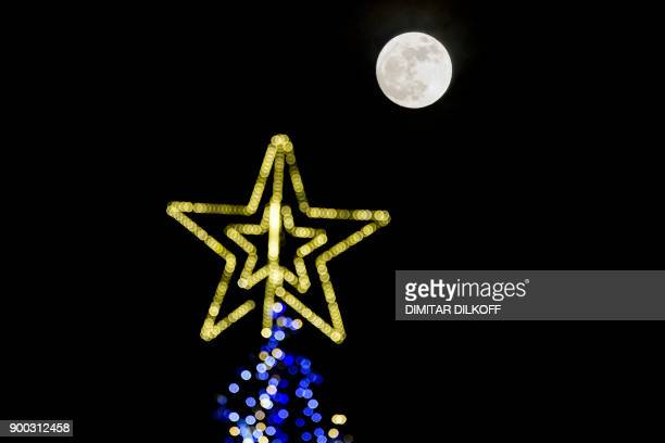 A picture taken on January 1 2018 shows the 'super moon' or 'wolf moon' rising over a Christmas tree in Sofia Supermoons happen when a full moon...