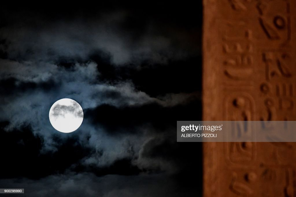TOPSHOT - A picture taken on January 1, 2018 shows the 'super moon' rising over Piazza del Popolo, in Rome. Supermoons happen when a full moon approximately coincides with the moon's perigee, or a point in its orbit at which it is closest to Earth. This makes the moon appear up to 14 percent larger and 30 percent brighter than usual. / AFP PHOTO / Alberto PIZZOLI