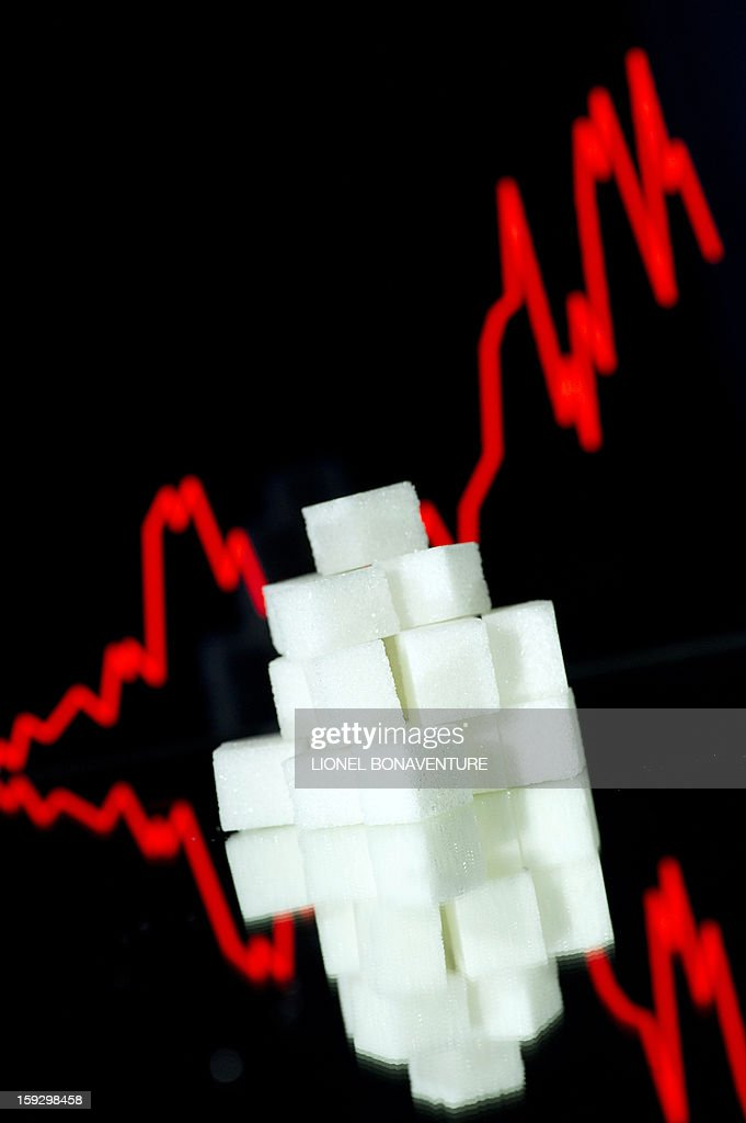 A picture taken on January 10, 2013 in Paris shows an illustration made with pieces of white sugar and a screen displaying the sugar exchange rate curve from 2002 to 2012. BONAVENTURE