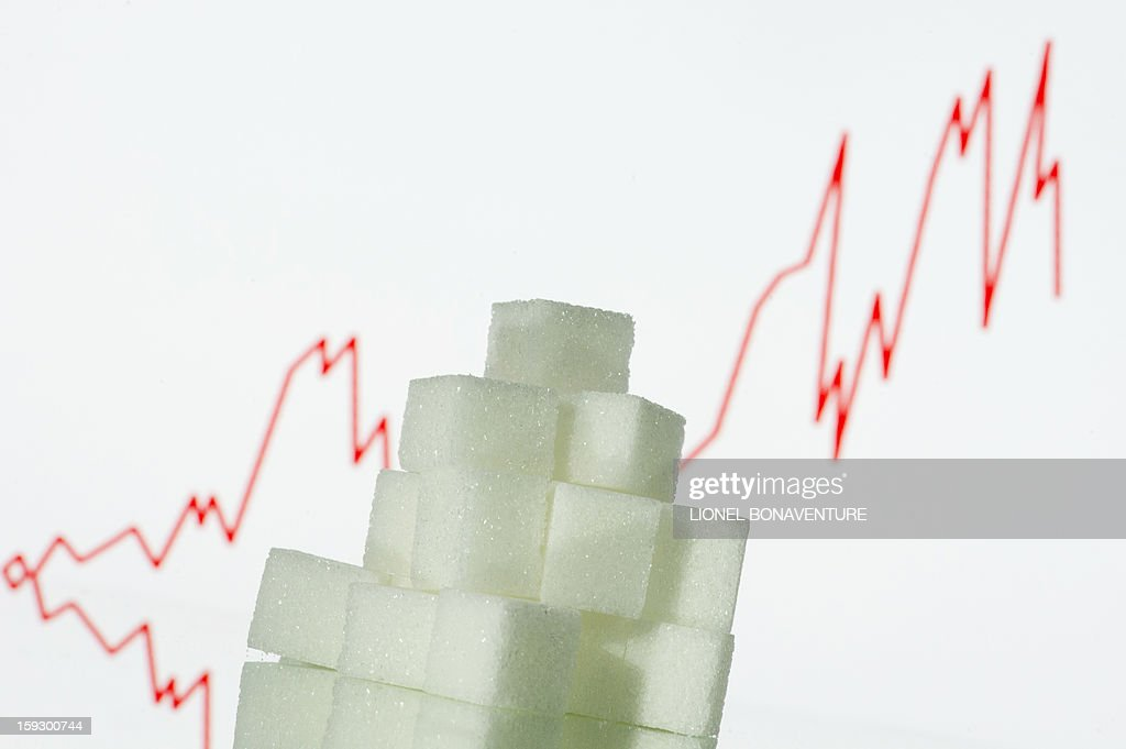 A picture taken on January 10, 2013 in Paris shows an illustration made with pieces of white sugar and a screen displaying the sugar exchange rate curve from 2002 to 2012