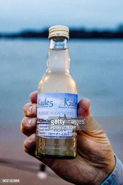 A picture taken on January 10 2018 shows a bottle with water from the Rhine sold by a cafe named Kade 5 in Tolkamer After heavy rains and snow melt...